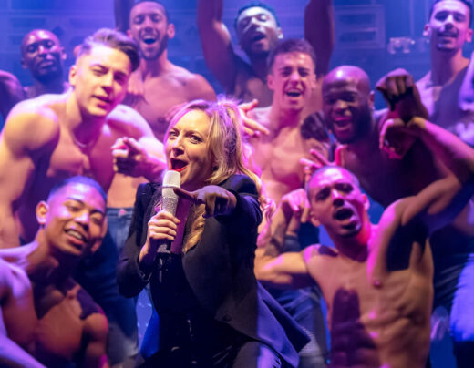 Woman signing into microphone surrounded by cast of Magic Mike